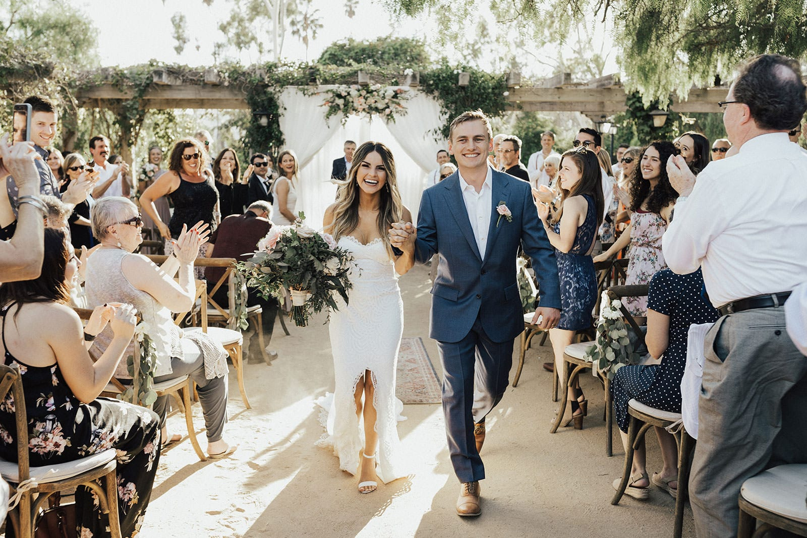 Blonde bride wearing Grace Loves Lace Paloma Gown holding bouquet walking down aisle with groom
