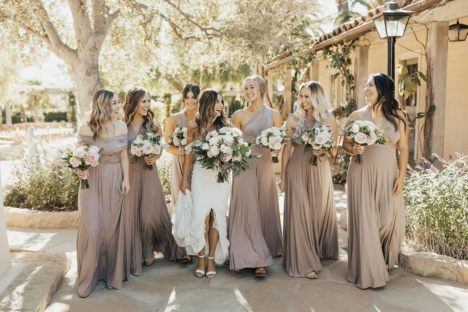 Blonde bride wearing Grace Loves Lace Paloma Gown standing with bridesmaids holding bouquets