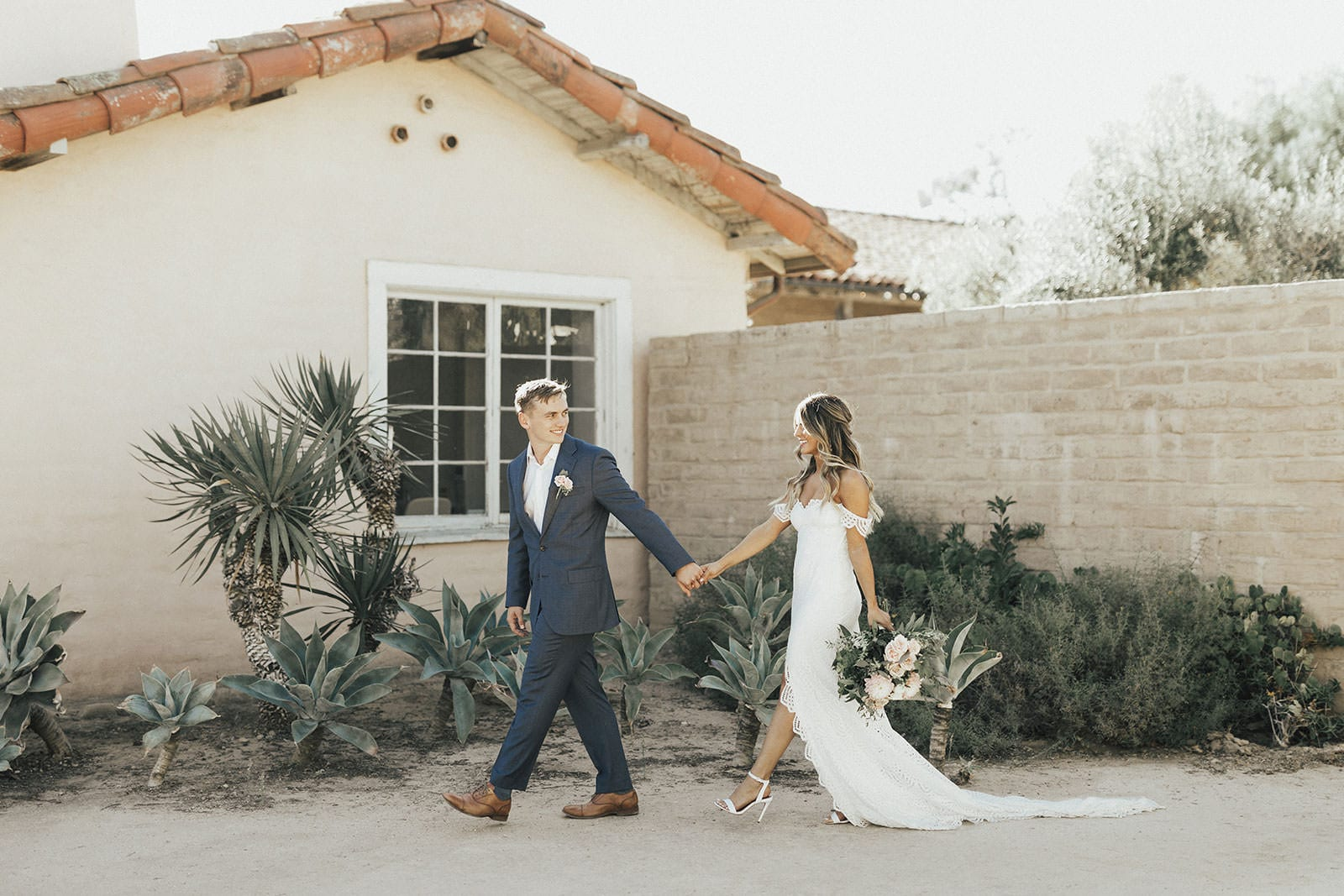 Blonde bride wearing Grace Loves Lace Paloma Gown holding hands with groom holding bouquet