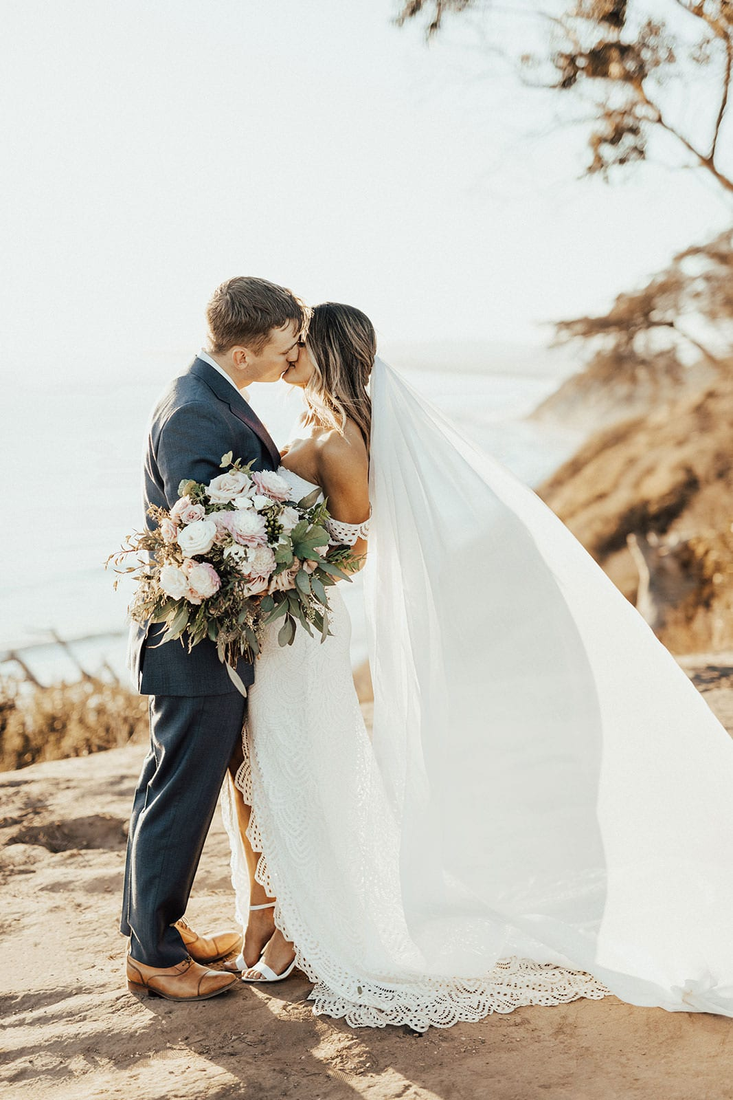 Blonde bride wearing Grace Loves Lace Paloma Gown kissing groom