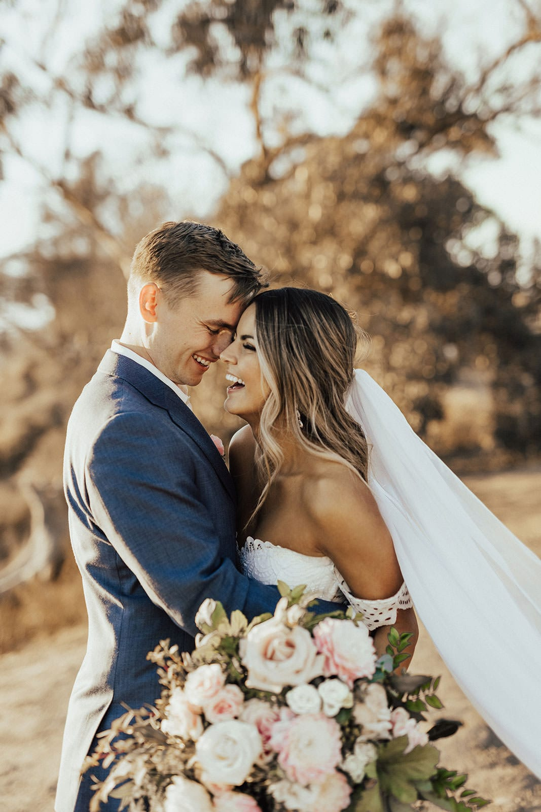 Blonde bride wearing Grace Loves Lace Paloma Gown being held by groom