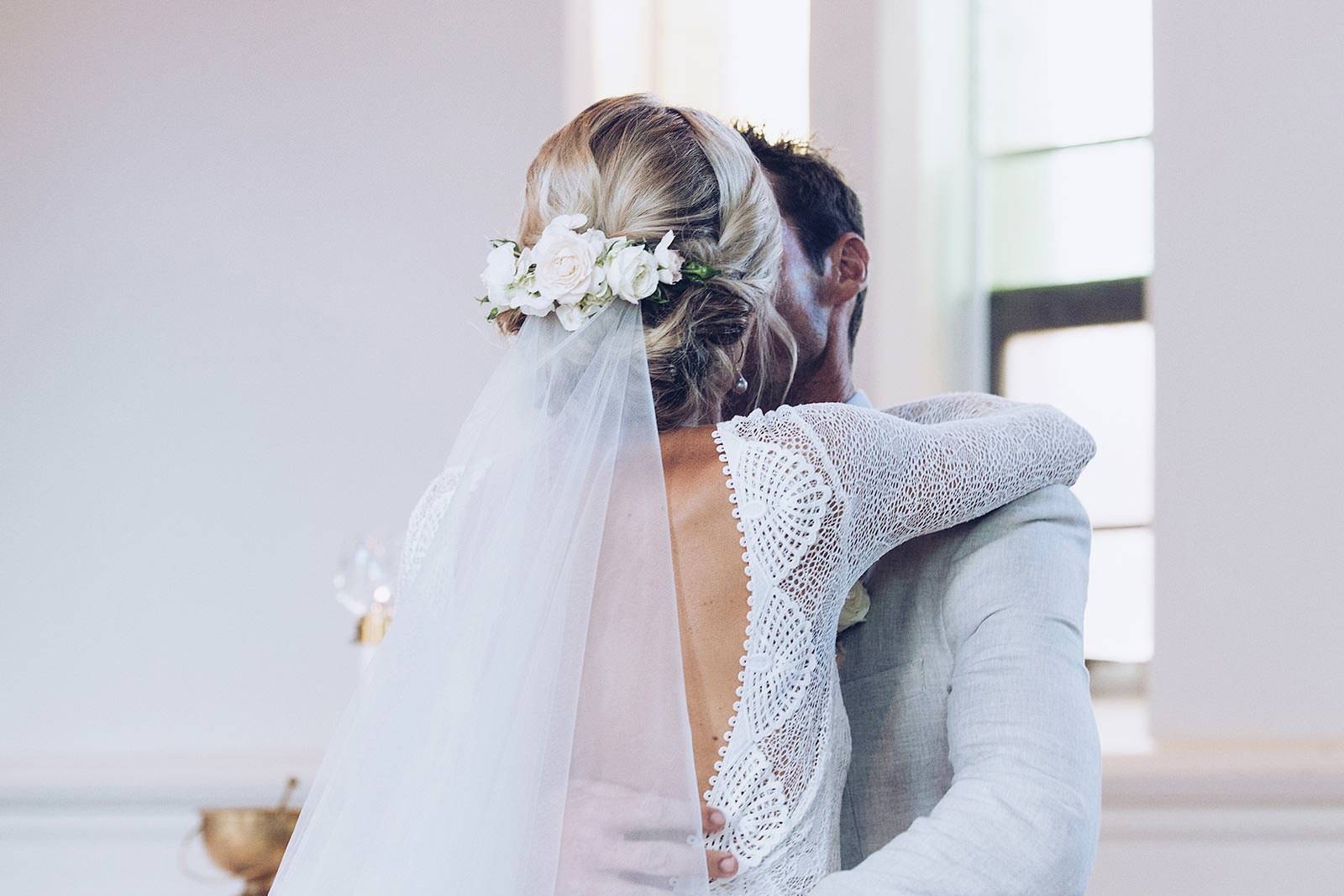 Back shot of bride wearing Grace Loves Lace Mai Gown kissing groom