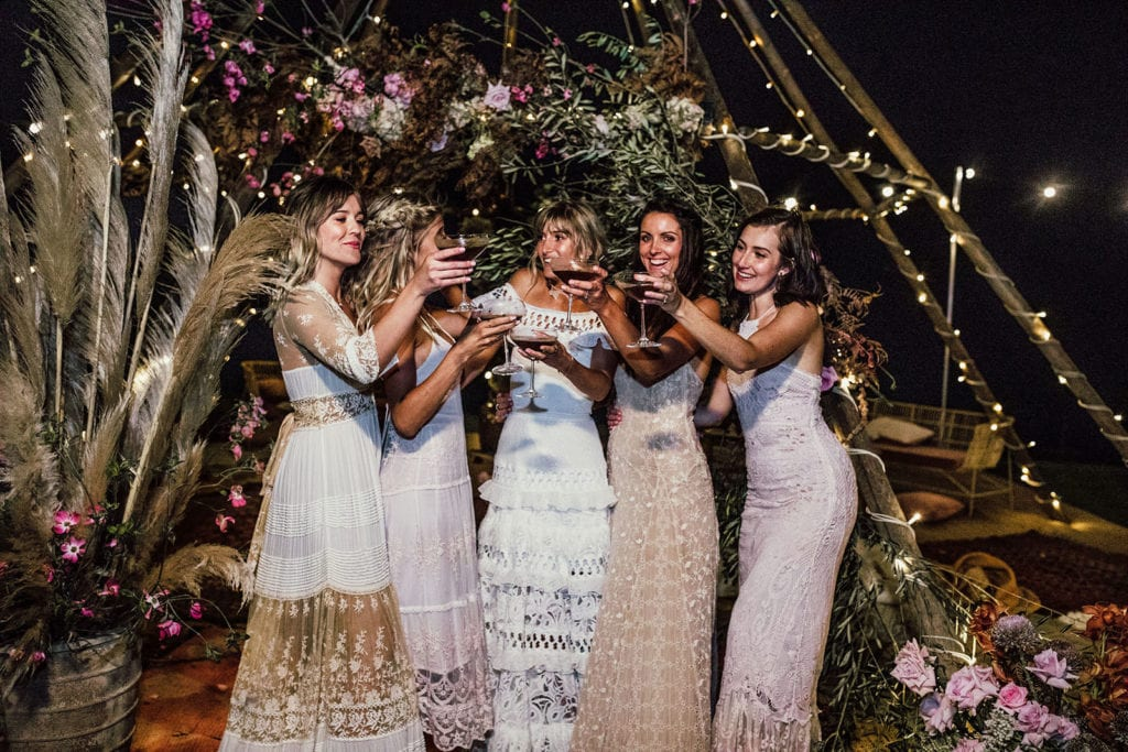 Blonde bride wearing Grace Loves Lace Coco Gown with bridesmaids holding wine glasses