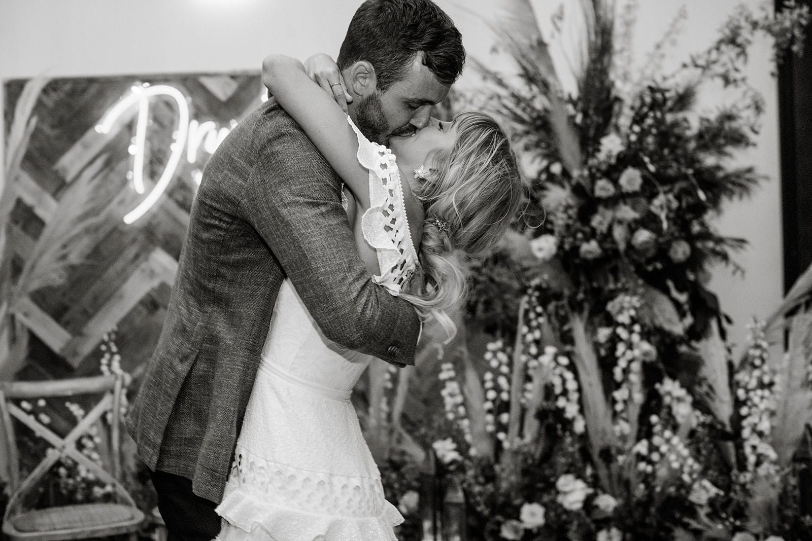 Black and white shot of bride wearing Grace Loves Lace Coco Gown kissing groom