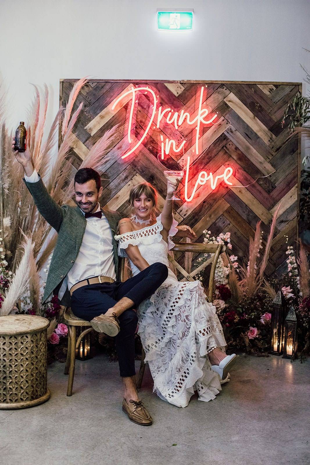 Blonde bride wearing Grace Loves Lace Coco Gown sitting with groom toasting in front of neon sign