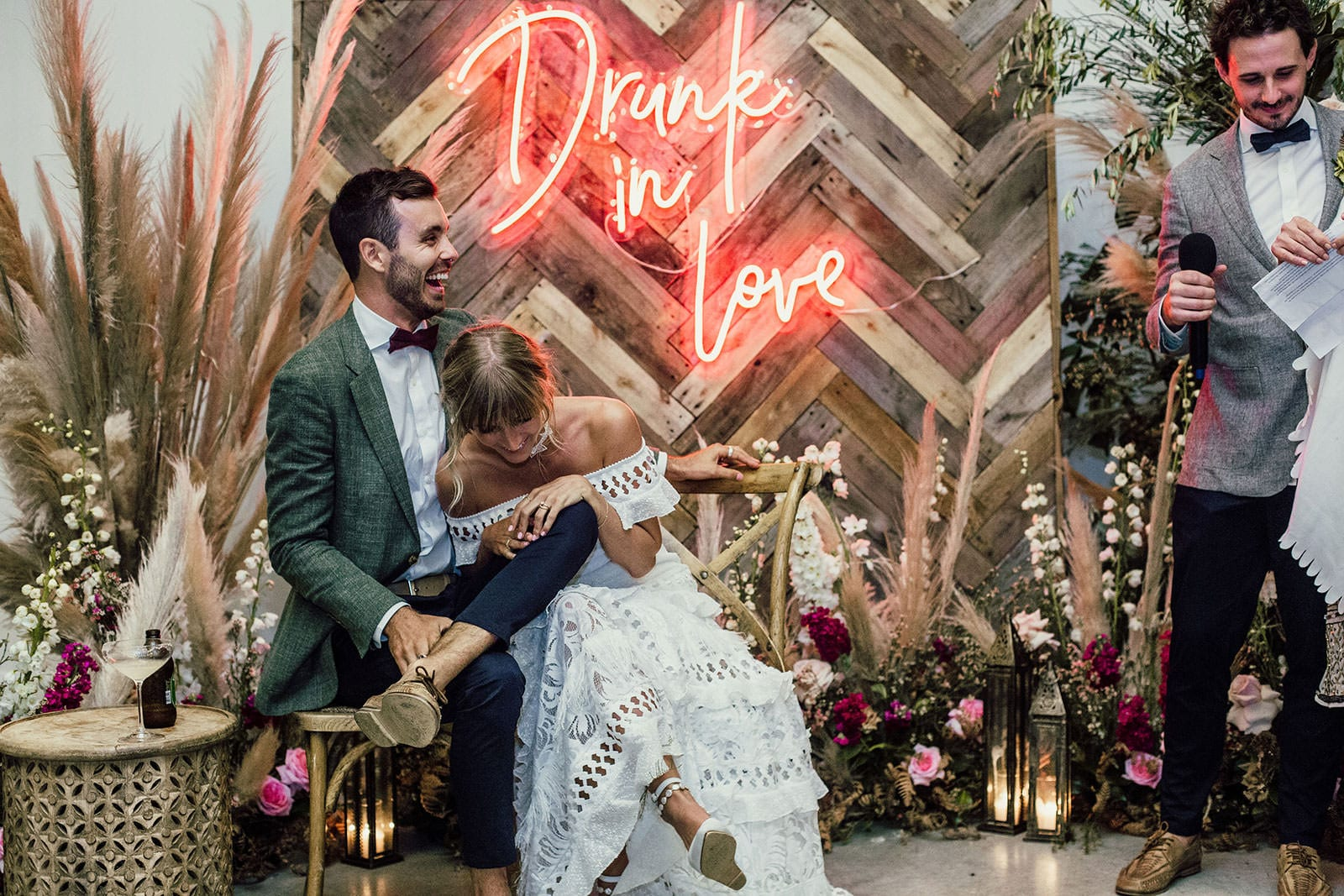 Blonde bride wearing Grace Loves Lace Coco Gown sitting with groom in front of neon sign