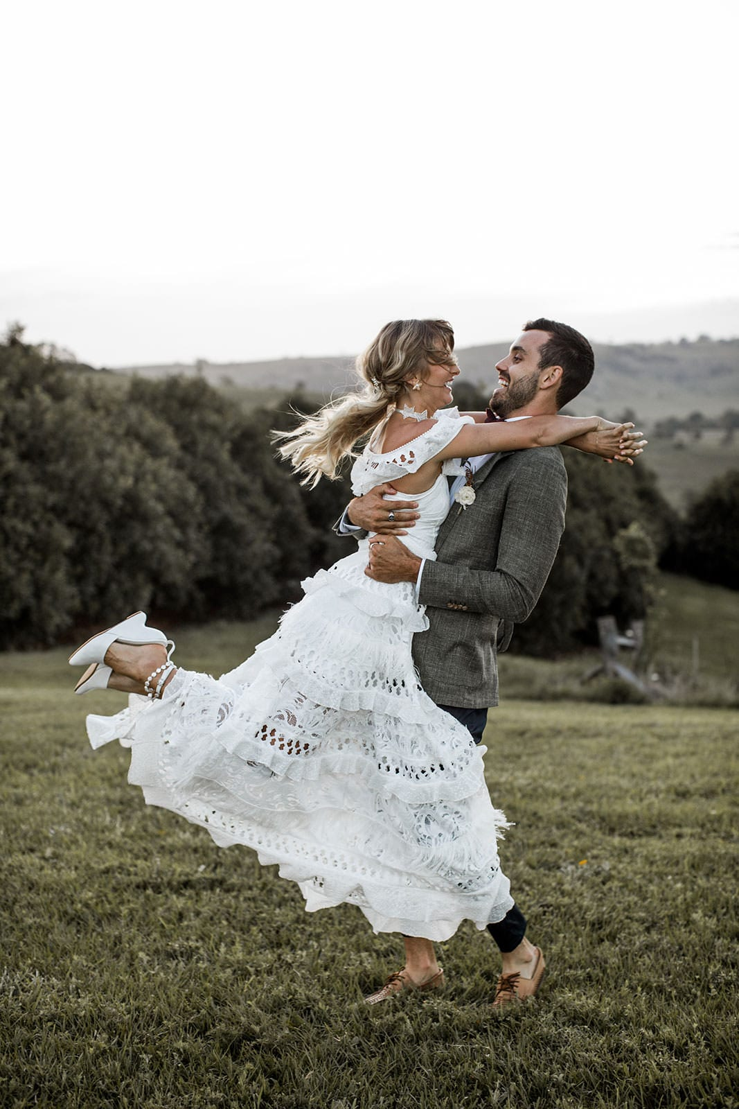 Blonde bride wearing Grace Loves Lace Coco Gown being held by groom