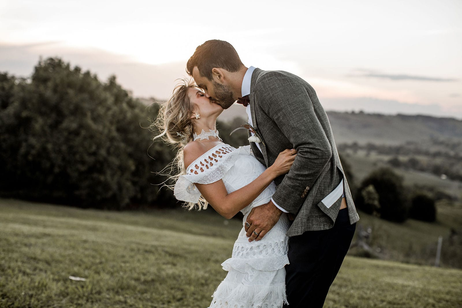 Blonde bride wearing Grace Loves Lace Coco Gown kissing groom
