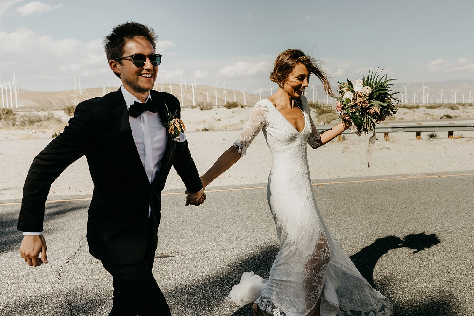 Blonde bride wearing Grace Loves Lace Francis Gown holding hands with groom holding bouquet on beach