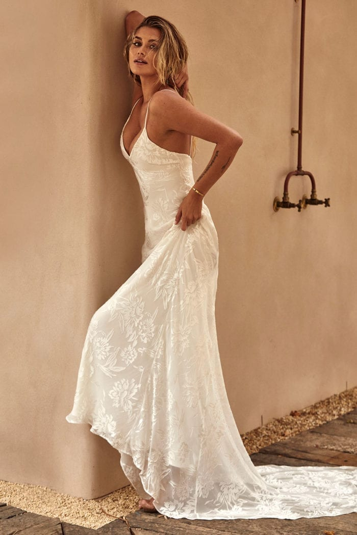 Blonde bride wearing Grace Loves Lace Loyola Gown leaning against wall