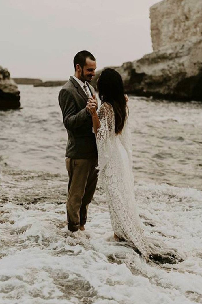 Bride wearing Grace Loves Lace Verdelle 2.0 Gown holding hands with groom standing in the surf
