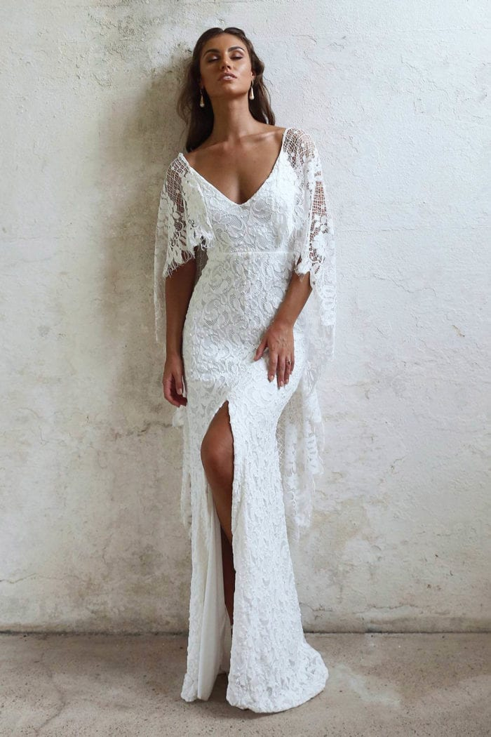 Bride wearing Grace Loves Lace Verdelle 2.0 Gown leaning against wall