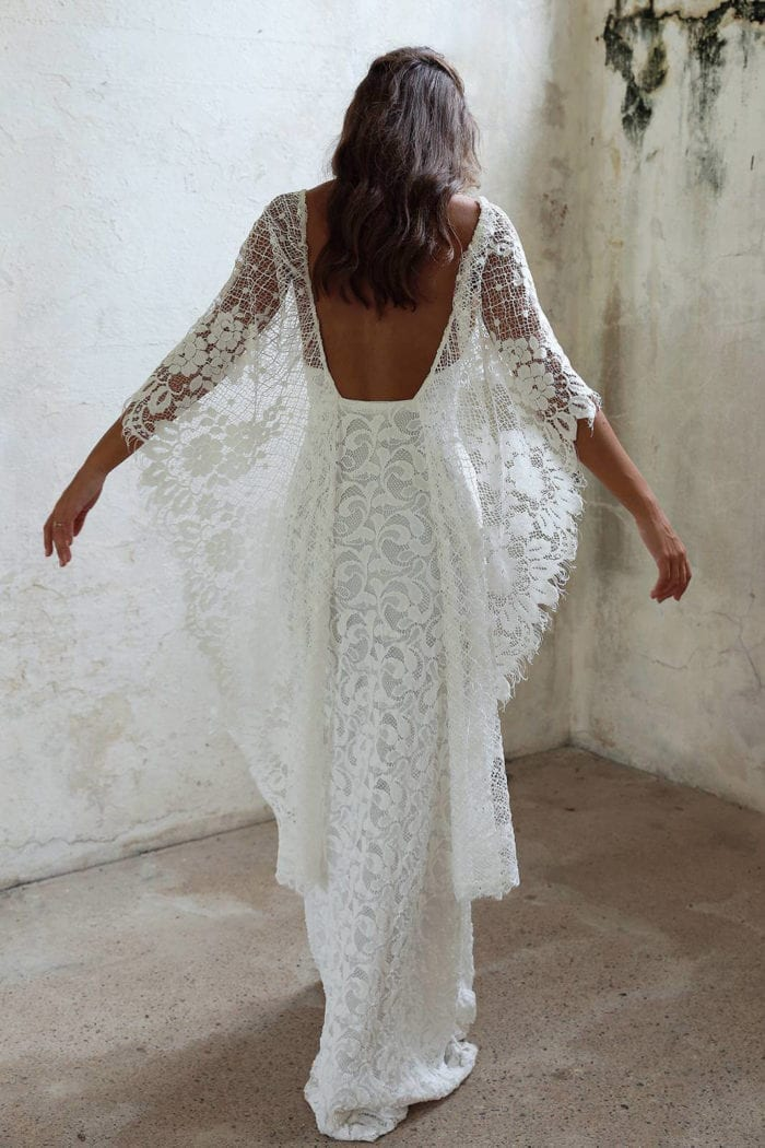 Back shot of bride wearing Grace Loves Lace Verdelle 2.0 Gown with arms outstretched