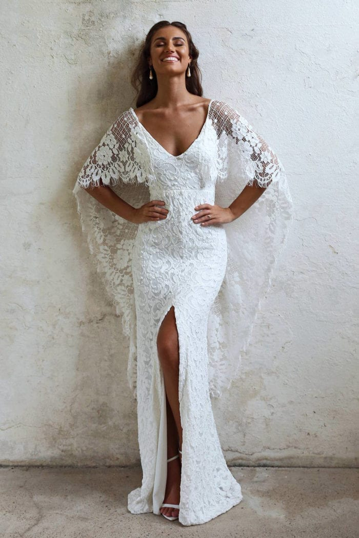 Bride wearing Grace Loves Lace Verdelle 2.0 Gown with hands on hips leaning against wall