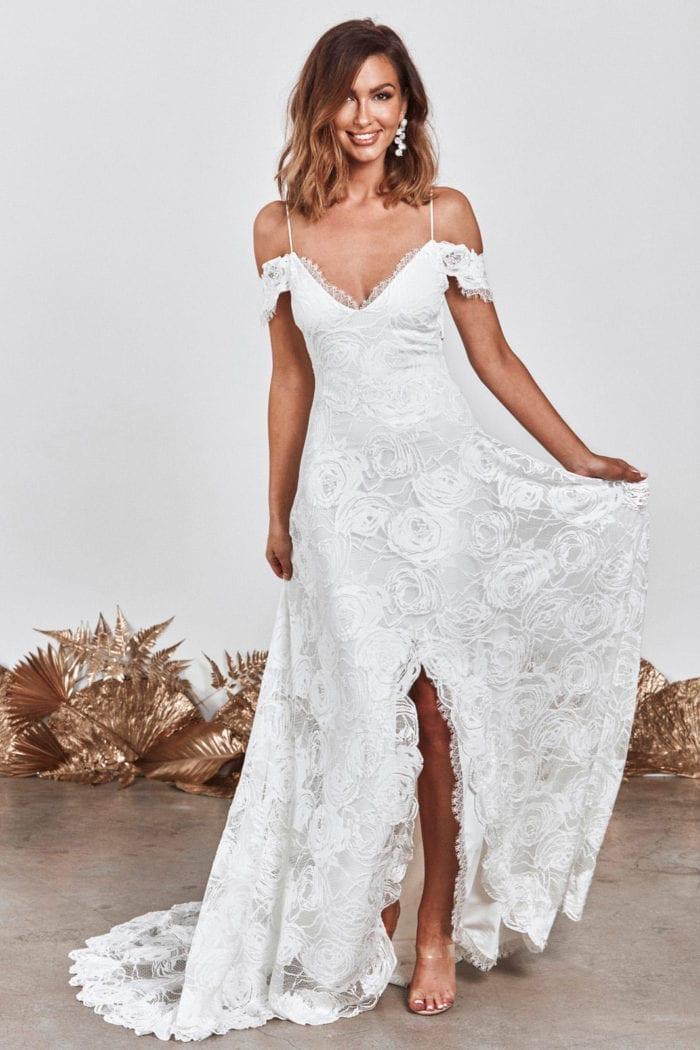 Bride wearing Grace Loves Lace Bonita Gown holding dress in one hand