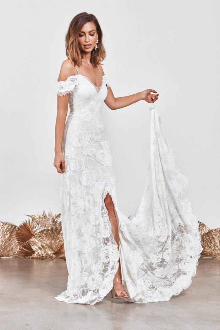 Bride wearing Grace Loves Lace Bonita Gown holding train in one hand