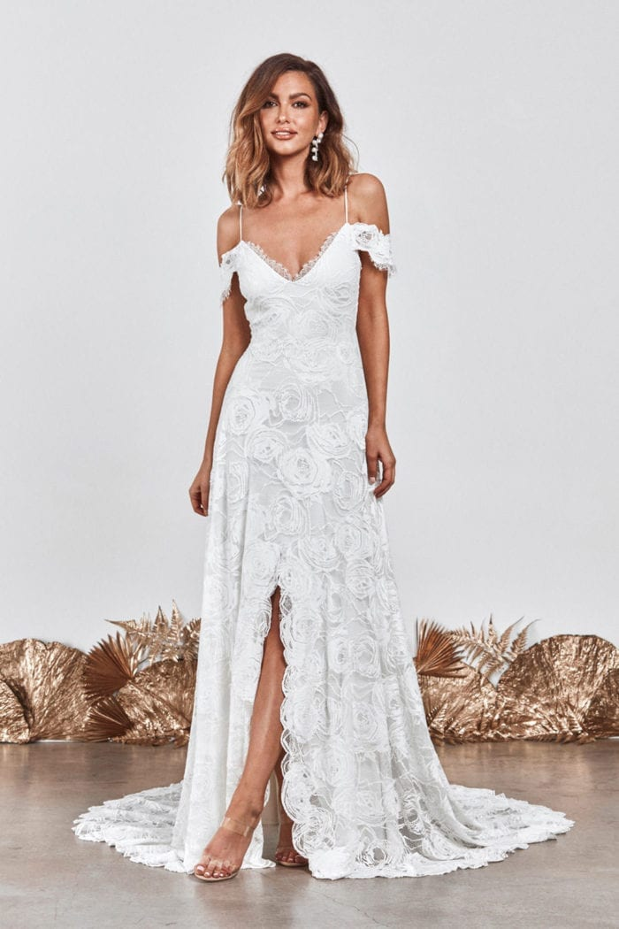 Bride wearing Grace Loves Lace Bonita Gown with one leg showing in skirt split