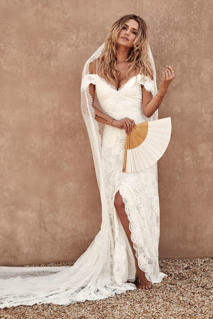 Bride wearing Grace Loves Lace Bonita Gown leaning against wall with veil over shoulders and fan in hand