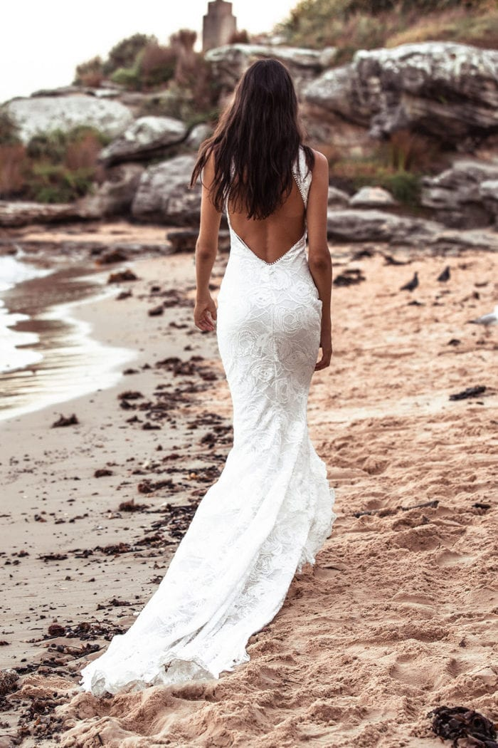 Back shot of bride wearing Grace Loves Lace Alexandra Rose Gown on beach