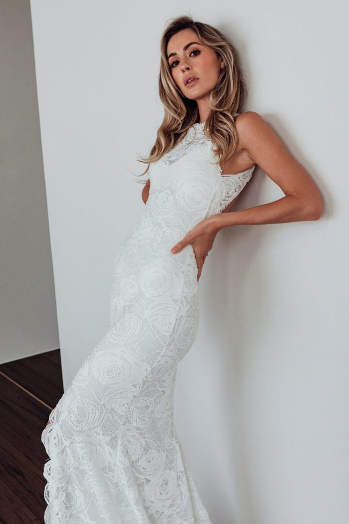 Bride wearing Grace Loves Lace Alexandra Rose Gown leaning against wall