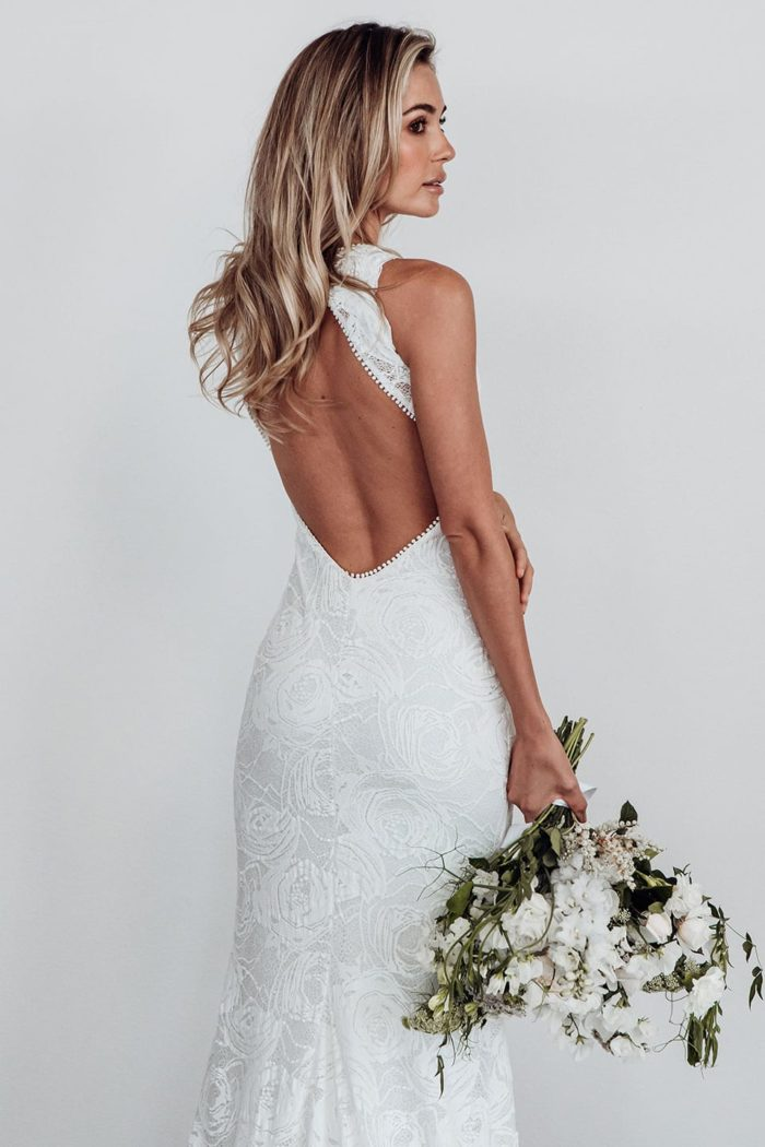 Back shot of bride wearing Grace Loves Lace Alexandra Rose Gown holding bouquet