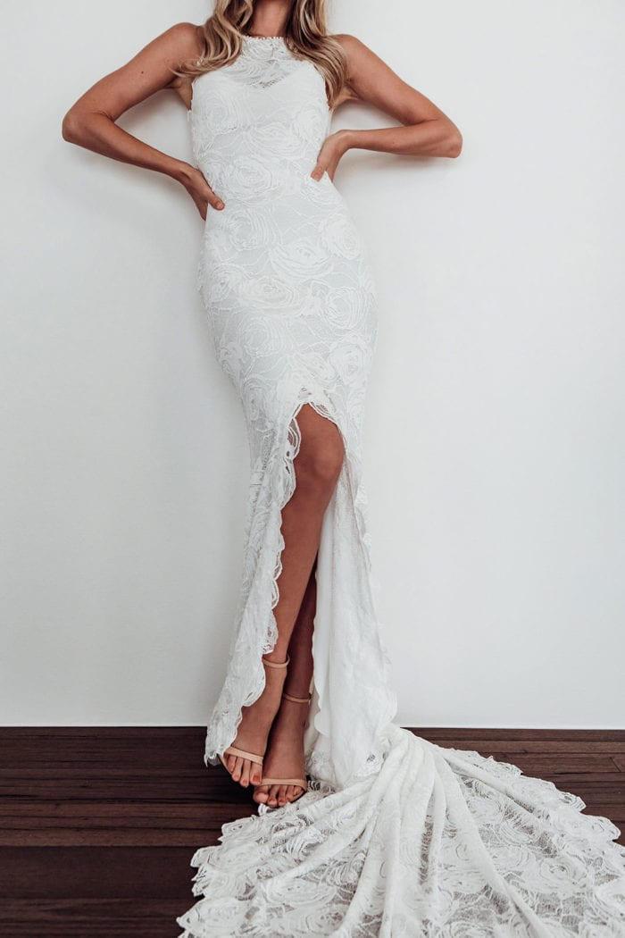 Bride wearing Grace Loves Lace Alexandra Rose Gown leaning against wall with hands on hips