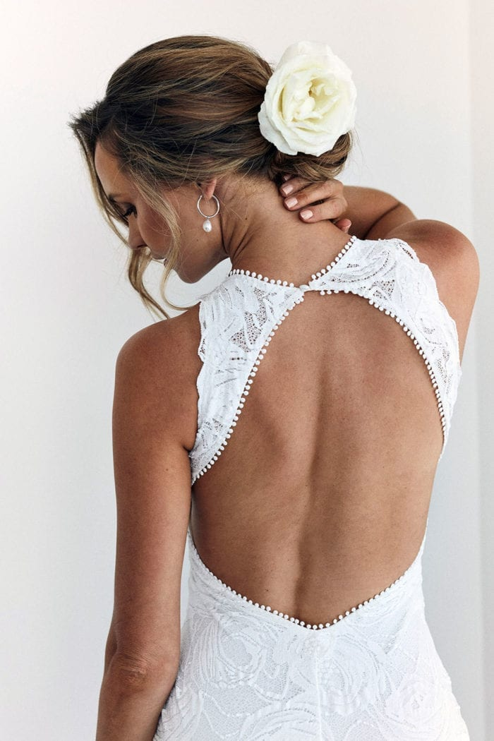 Back shot of bride wearing Grace Loves Lace Alexandra Rose Gown with flower in hair and hand on neck
