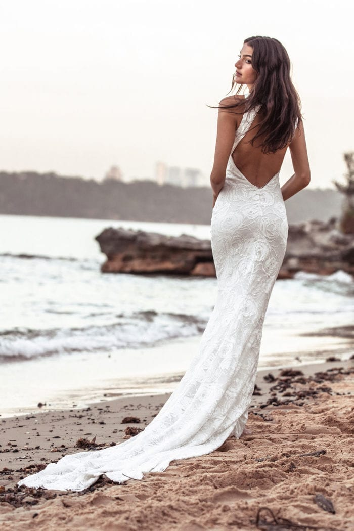 Back shot of bride wearing Grace Loves Lace Alexandra Rose Gown walking along beach