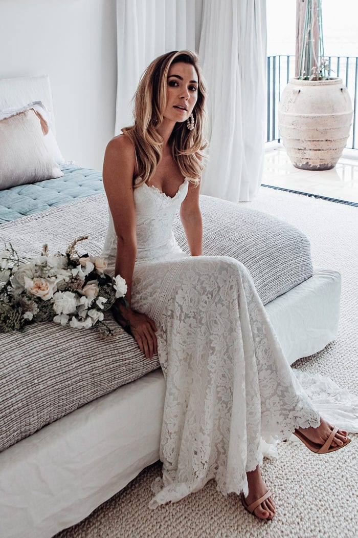 Bride wearing Grace Loves Lace Hart Gown sitting on bed with bouquet