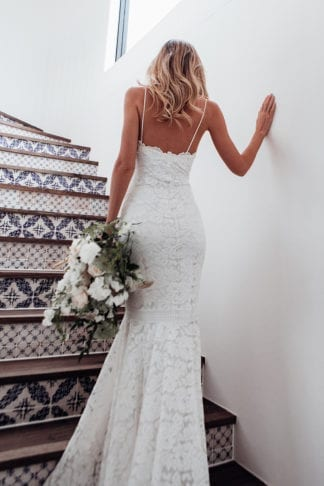 Back shot of bride wearing Grace Loves Lace Hart Gown holding bouquet walking up stairs