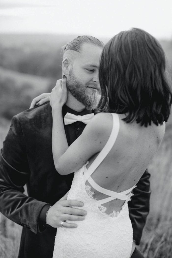 Black and white shot of bride wearing Grace Loves Lace Nia 2.0 Gown embracing groom