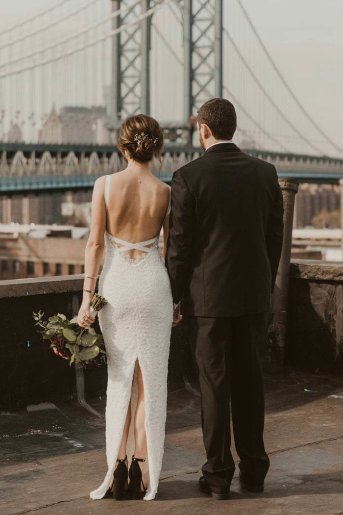 Back shot of bride wearing Grace Loves Lace Nia 2.0 Gown standing with groom holding bouquet