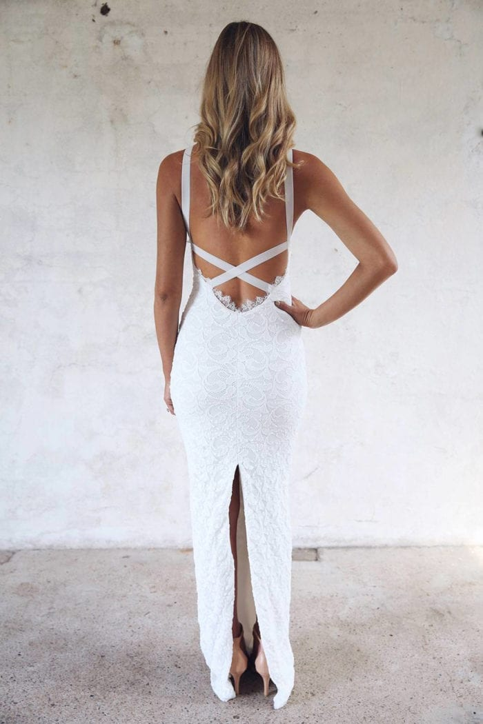 Back shot of blonde bride wearing Grace Loves Lace Nia 2.0 Gown with hand on hip