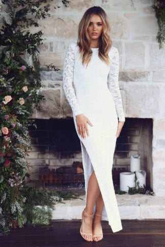 Blonde bride wearing Grace Loves Lace Kiki 2.0 Gown standing in front of fireplace
