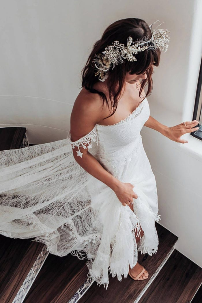 Brunette bride wearing Grace Loves Lace Fabienne 2.0 Gown walking down stairs