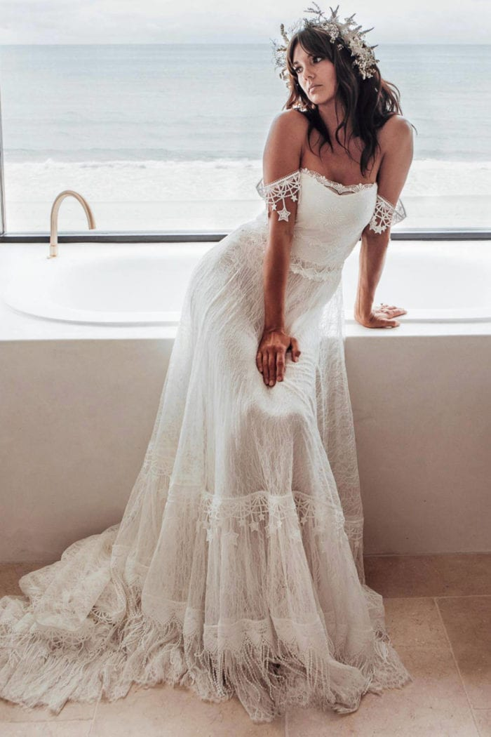 Brunette bride wearing Grace Loves Lace Fabienne 2.0 Gown leaning on bathrub