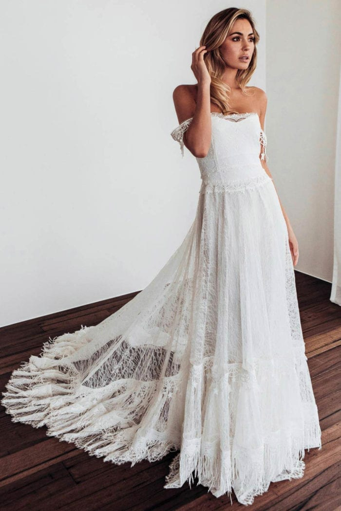 Blonde bride wearing Grace Loves Lace Fabienne 2.0 Gown with hand on hair