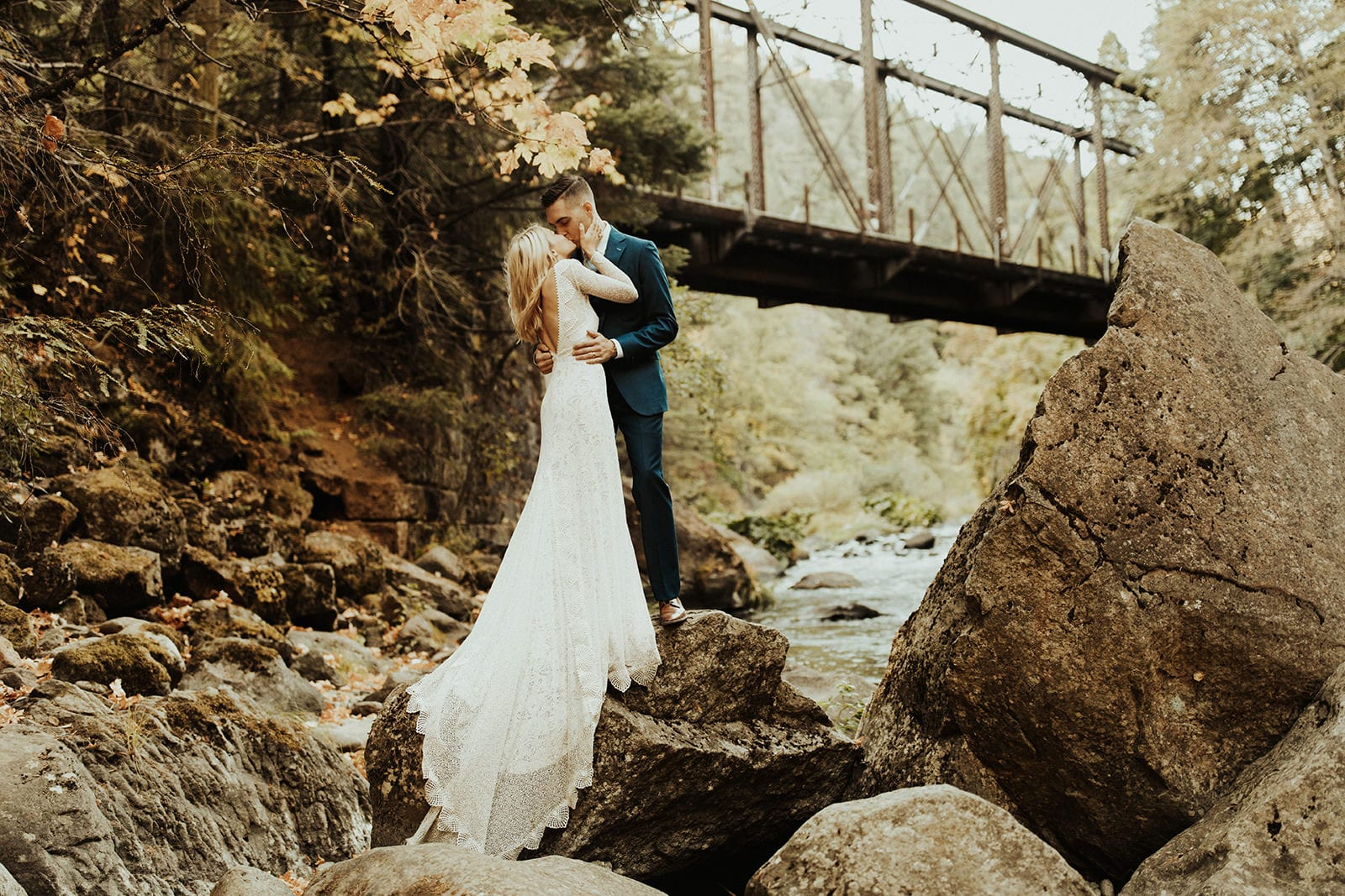 Blonde bride wearing Grace Loves Lace Mai Gown kissing groom near river and bridge