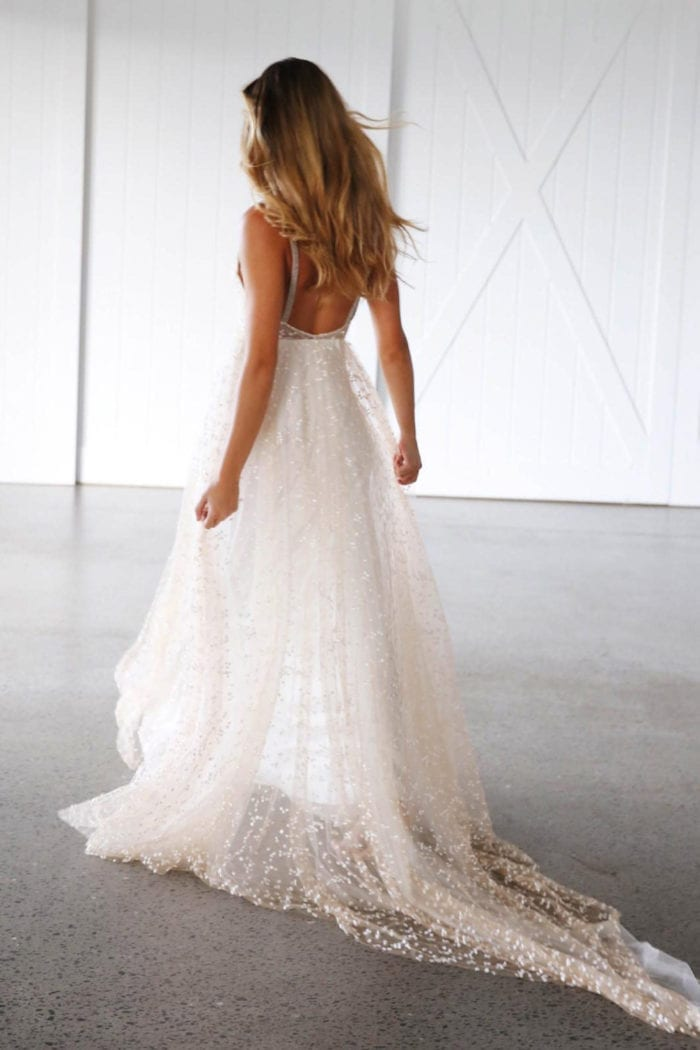 Back shot of blonde bride wearing Grace Loves Lace Menha Gown holding skirt in hands