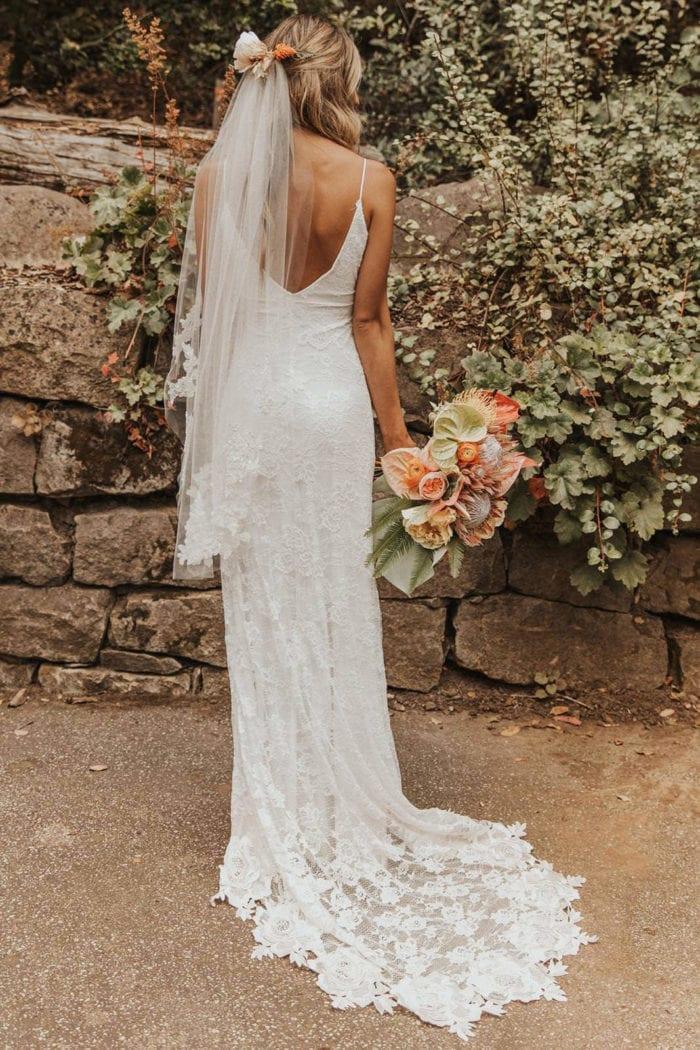 Back shot of bride wearing Grace Loves Lace Lottie Gown holding bouquet