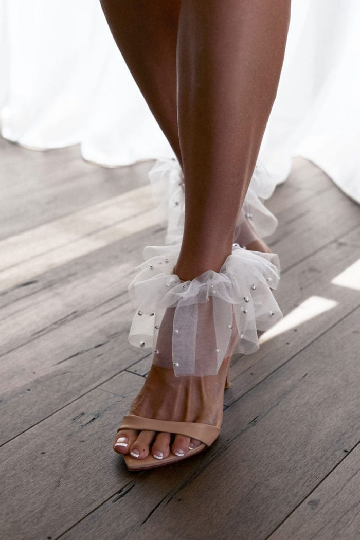 Close-up of bride wearing Grace Loves Lace Pearly Anklets