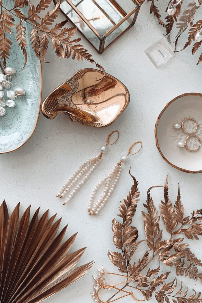 Grace Loves Lace Mata Earrings on table surrounded by rose gold items
