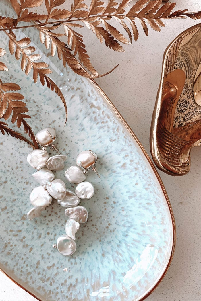 Grace Loves Lace Essie Earrings displayed in sky blue dish with rose gold accessories