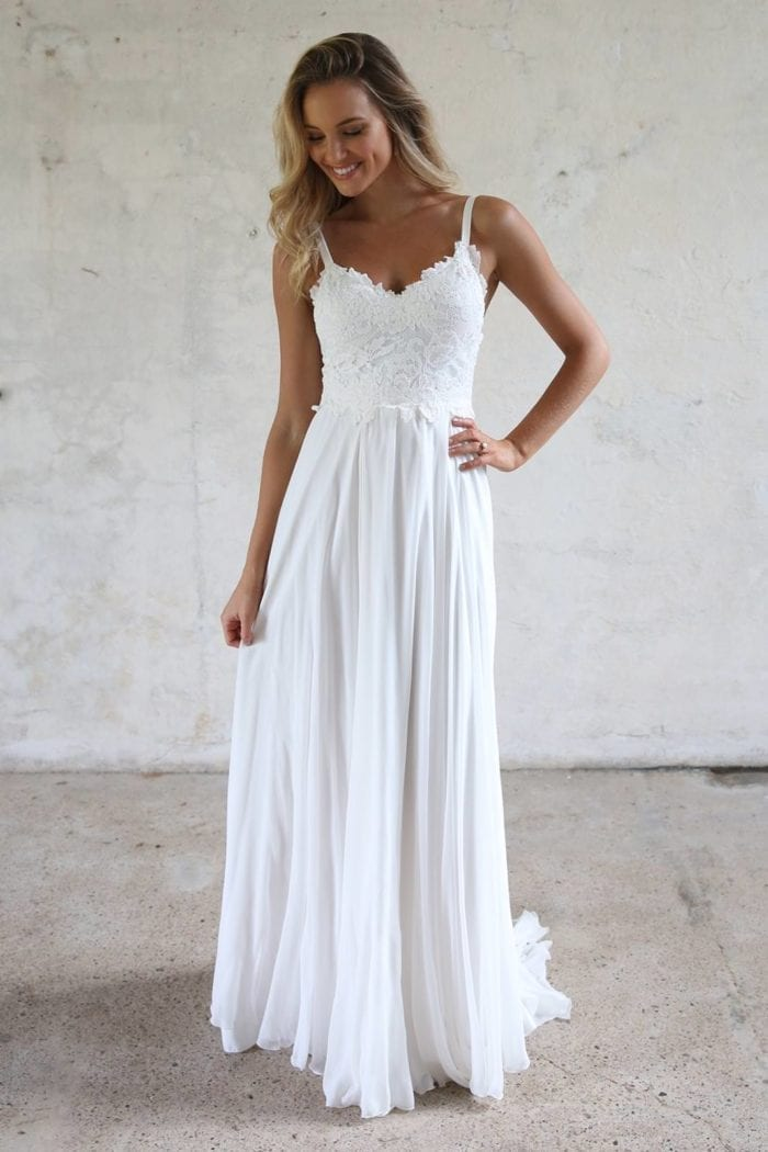 Blonde bride wearing Grace Loves Lace Tara Gown with hand on hip