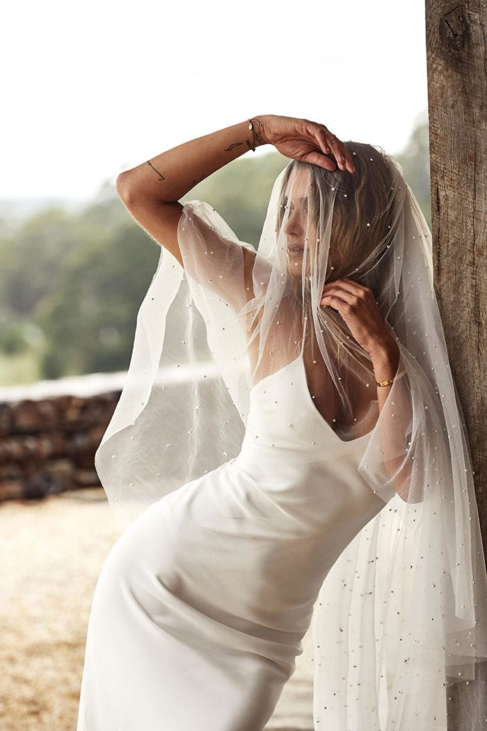 Bride wearing Grace Loves Lace Summer Gown leaning against post with veil over face