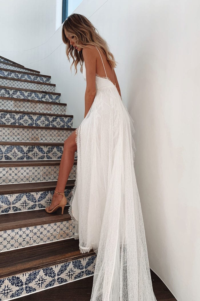 Back shot of bride wearing Grace Loves Lace Song Gown on stairs