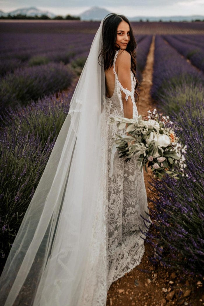 Back shot of bride wearing Grace Loves Lace Sol Gown holding bouquet in field of lavender