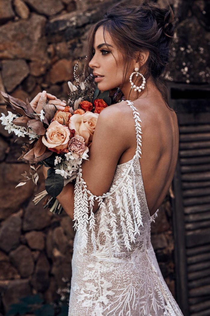 Back shot of bride wearing Grace Loves Lace Sol Gown holding bouquet