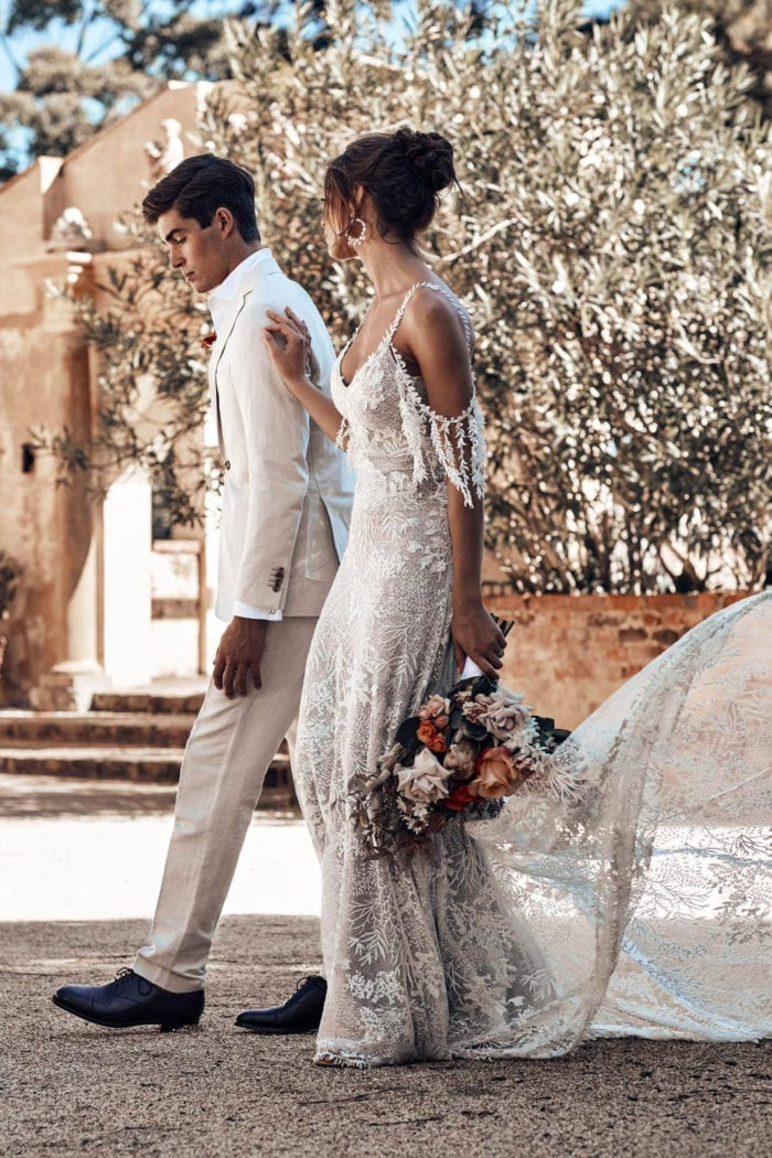 Bride wearing Grace Loves Lace Sol Gown holding bouquet walking with groom