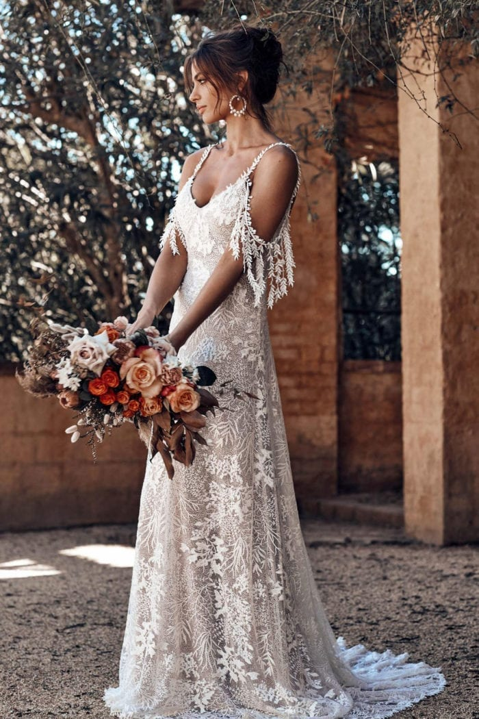 Bride wearing Grace Loves Lace Sol Gown holding bouquet